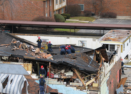 Firemen on top of collapsed roof