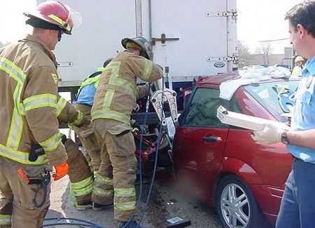 Firemen using tool on car