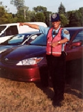 A traffic director stands in front of a line of cars and points to the left