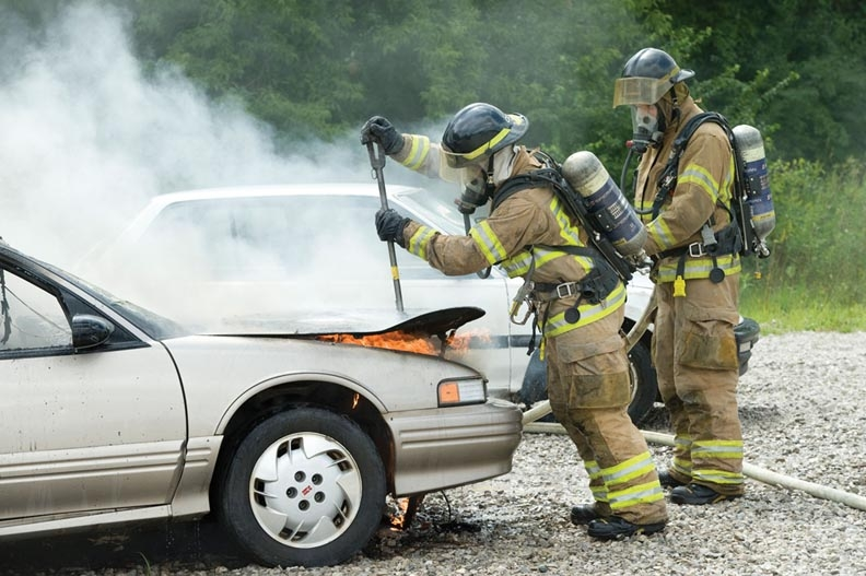 Two fireman help to put out a car fire.