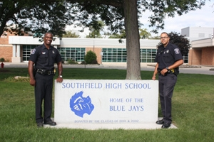 Two officers stand in front of Southfield High School