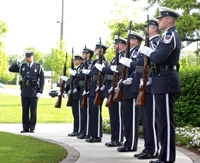 A line of soldiers stand listening to an officer