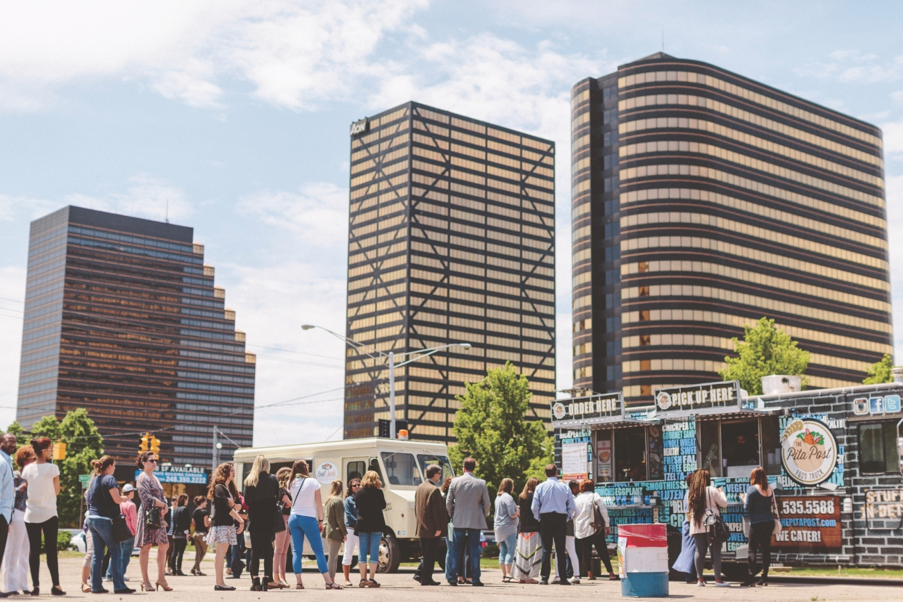 Skyline with group of people standing in line at a food truck